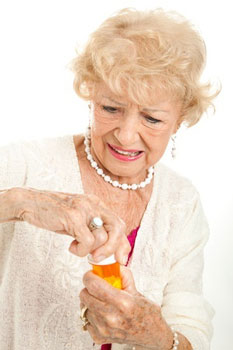 Woman with arthritis opening medicine